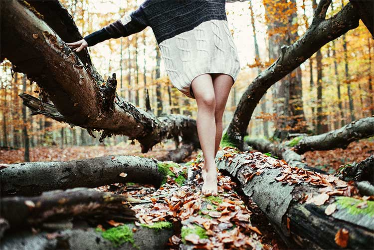 Bare legs and feet of a woman in a long woolen sweater balancing on a tree's root system
