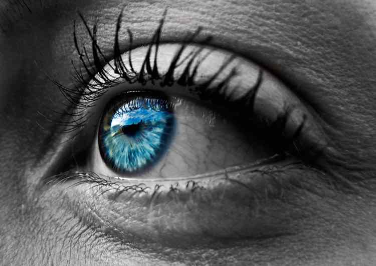 A closeup of an eye in black and white, with a blue-green iris in color