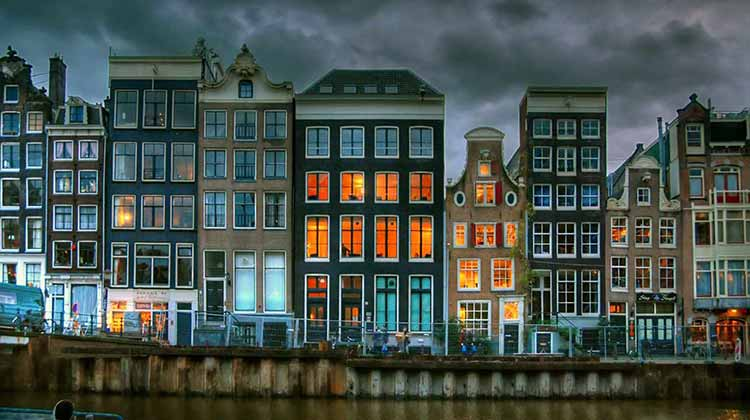 A row of houses with lit windows along an Amsterdam canal