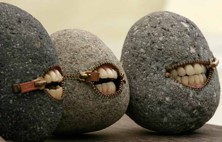 A set of smiling stones with human teeth and zipper mouths