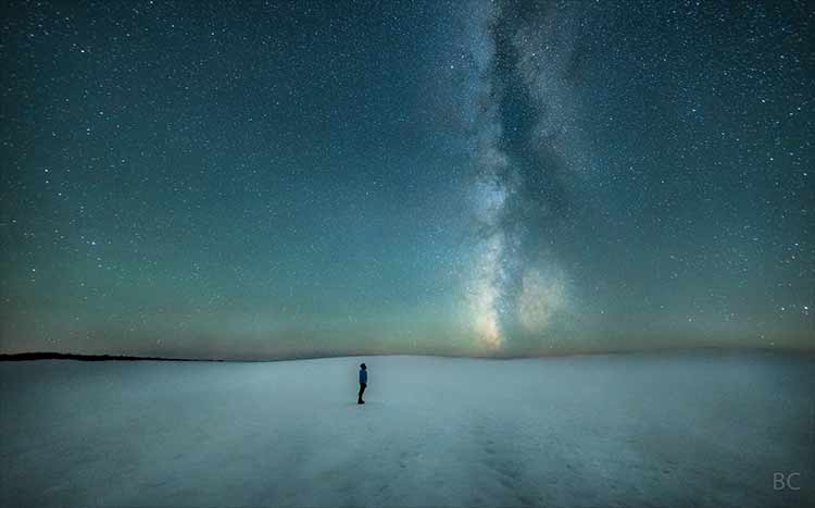 Photograph of a man standing at the summit of the South Sister volcano in Oregon, under the Milky Way