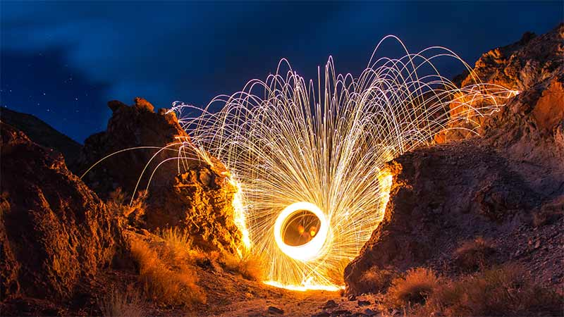 Sparks from burning steel wool arcing in a small canyon at night