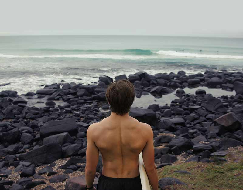 A male surfer in front of a rocky beach, seen from behind